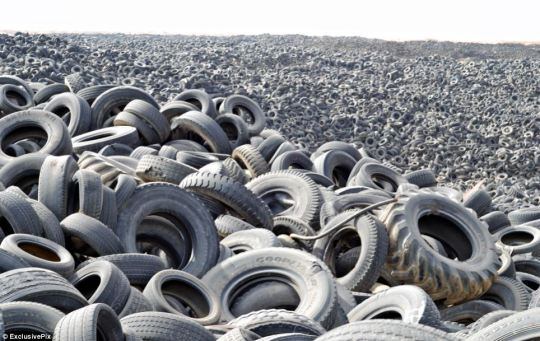 A sea of rubber: In Kuwait City's Sulaibiya area every year gigantic holes are dug out in the sandy earth and filled with old tyres - there are now over seven million in the ground.